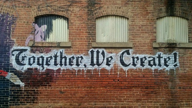 "Graffiti on a wall ""Together we create"""